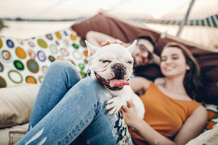 Cute dog smiling while on a trip with his owners, joyful young family lying in comfortable hammock