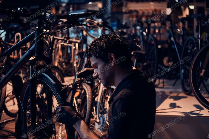 Diligent attractive mechanic is repairing customer's bicycle at workplace