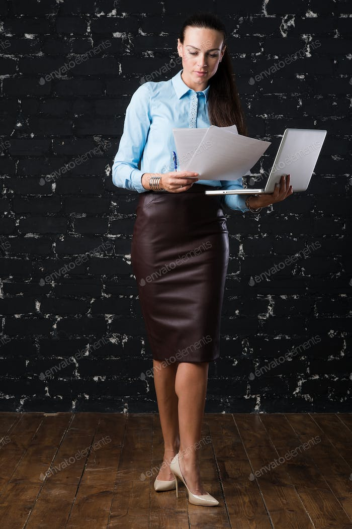 Young businesswoman holding a laptop, standing on office