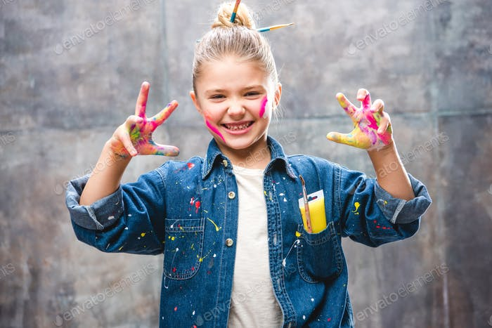 Schoolgirl artist with painted face showing palms in paint and smiling at camera