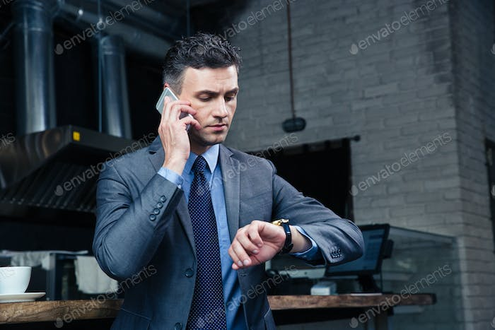 Confident businessman speaking on the phone in cafe