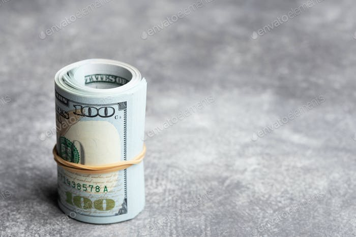 Roll of Money on Stone Background.