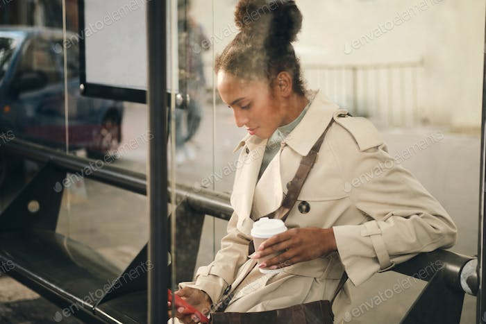 Attractive African American girl in stylish trench coat dreamily using cellphone at bus stop