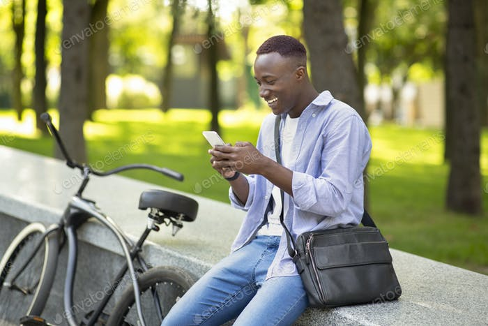 Positive black man with bike writing message on cellphone at urban park