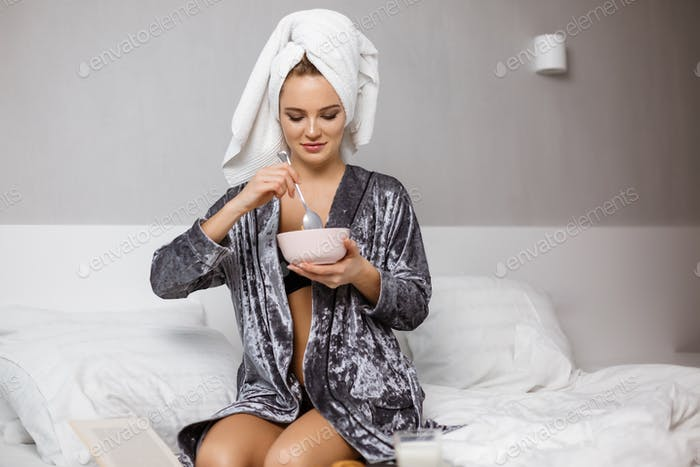 Young smiling lady in velvet robe sitting in bed with towel on head and holding bowl with spoon