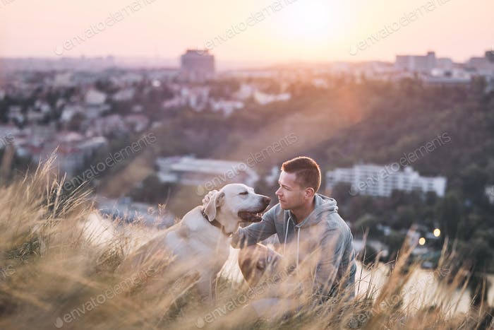 Young man and his labrador retriever at sunrise