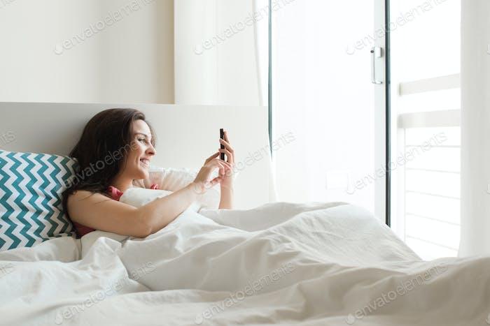Frau im Bett mit Smartphone