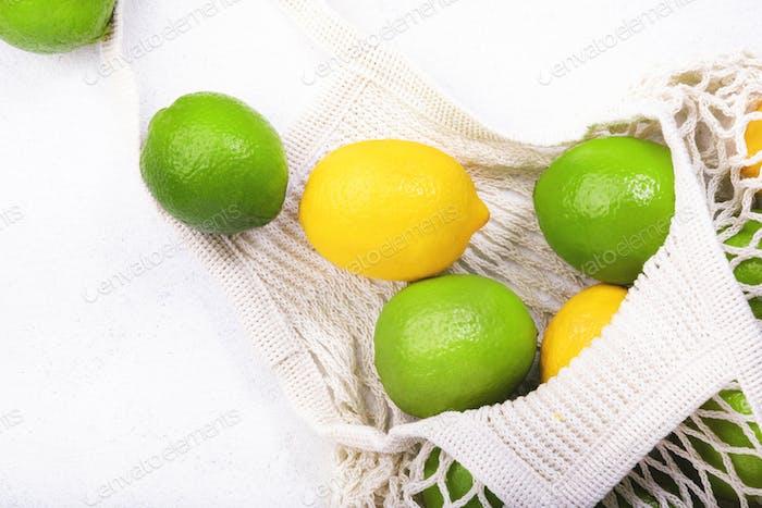Organische Zitronen und Limetten in wiederverwendbarem, umweltfreundlichem Netzbeutel