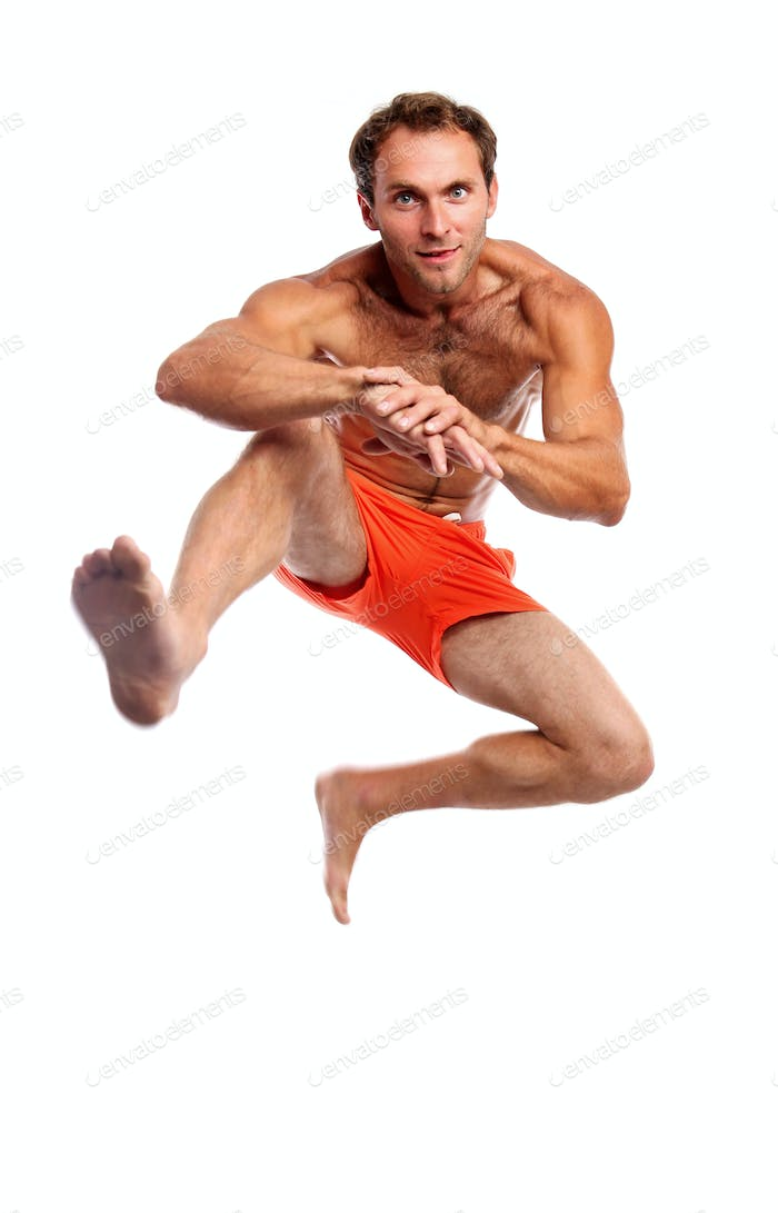 Young muscular man jumping against white