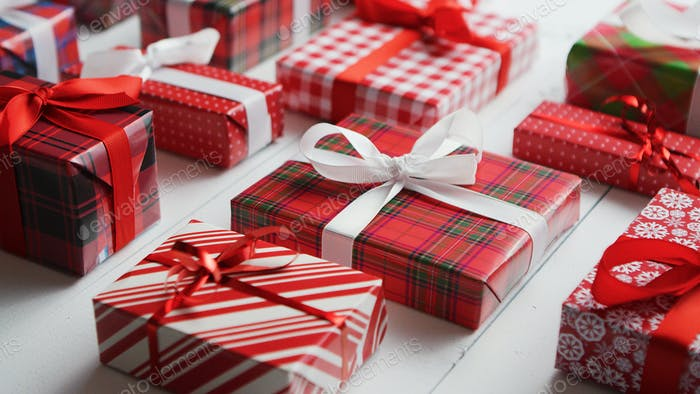 Side view of wrapped Christmas presents laid on the wooden table