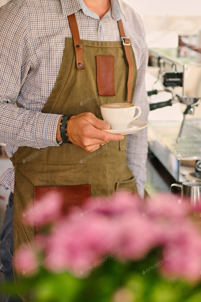 Image of male preparing coffee in a coffee machine.
