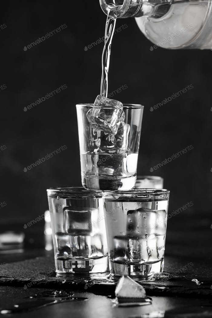 Vodka in shot glasses pouring out of the bottle on black stone background, iced strong drink