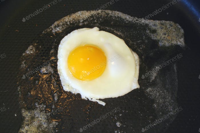 Sunnyside up egg frying in a pan