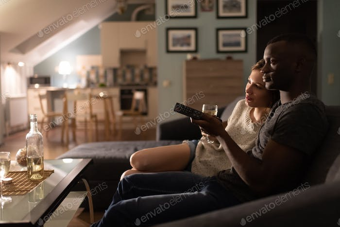 Loving multiracial couple watching movie during date