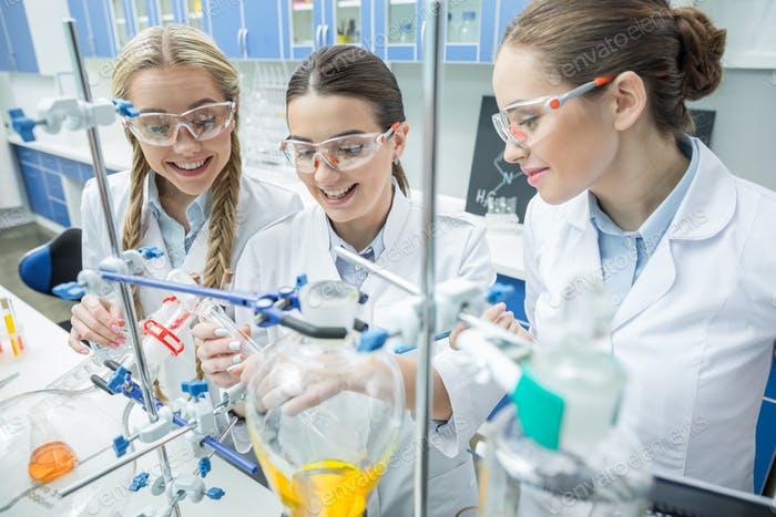 Smiling female scientists in protective eyewear making experiment in chemical laboratory