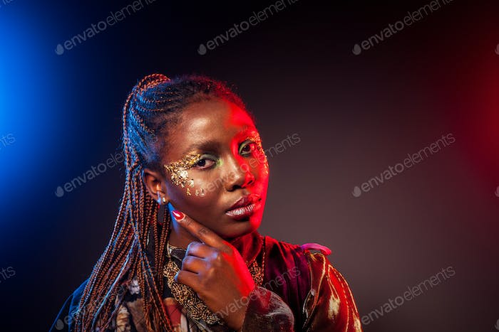 Young African woman with afro hairstyle and golden shiny makeup. Studio shot.