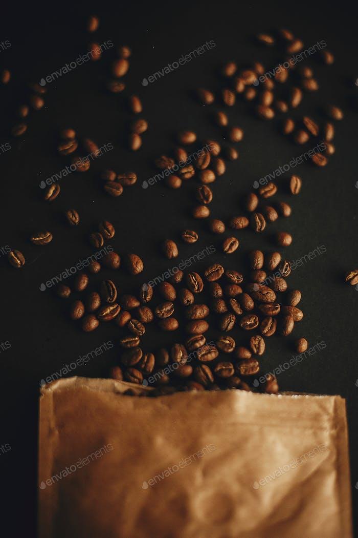 Kaffeebohnen verstreut aus Papierpackung auf schwarzem Hintergrund Flach lag