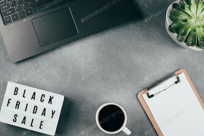 Flat lay with copy space. Black friday sale word on lightbox, laptop, coffee, empty blank, succulent