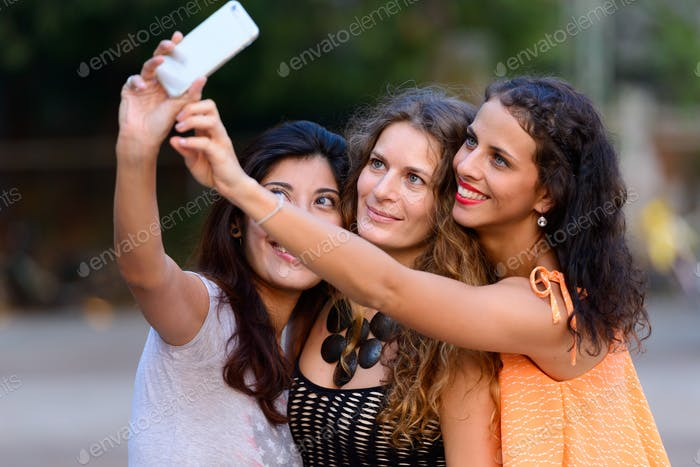 Three young beautiful women as friends together outdoors