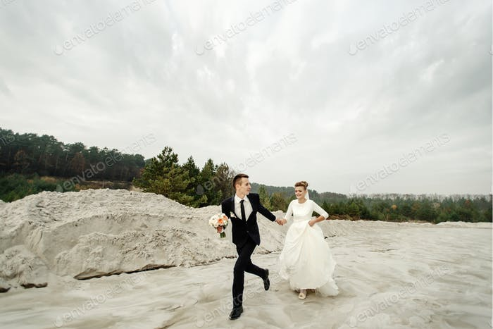 happy bride and groom having fun and running, luxury elegant wedding at the beach
