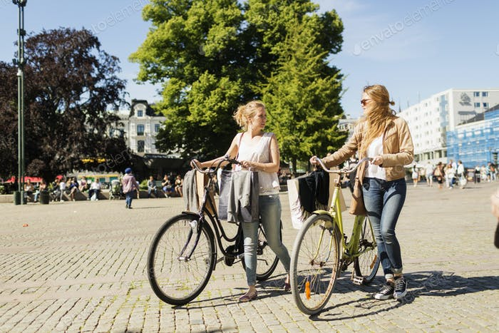 Shopaholic friends walking with bicycles in city