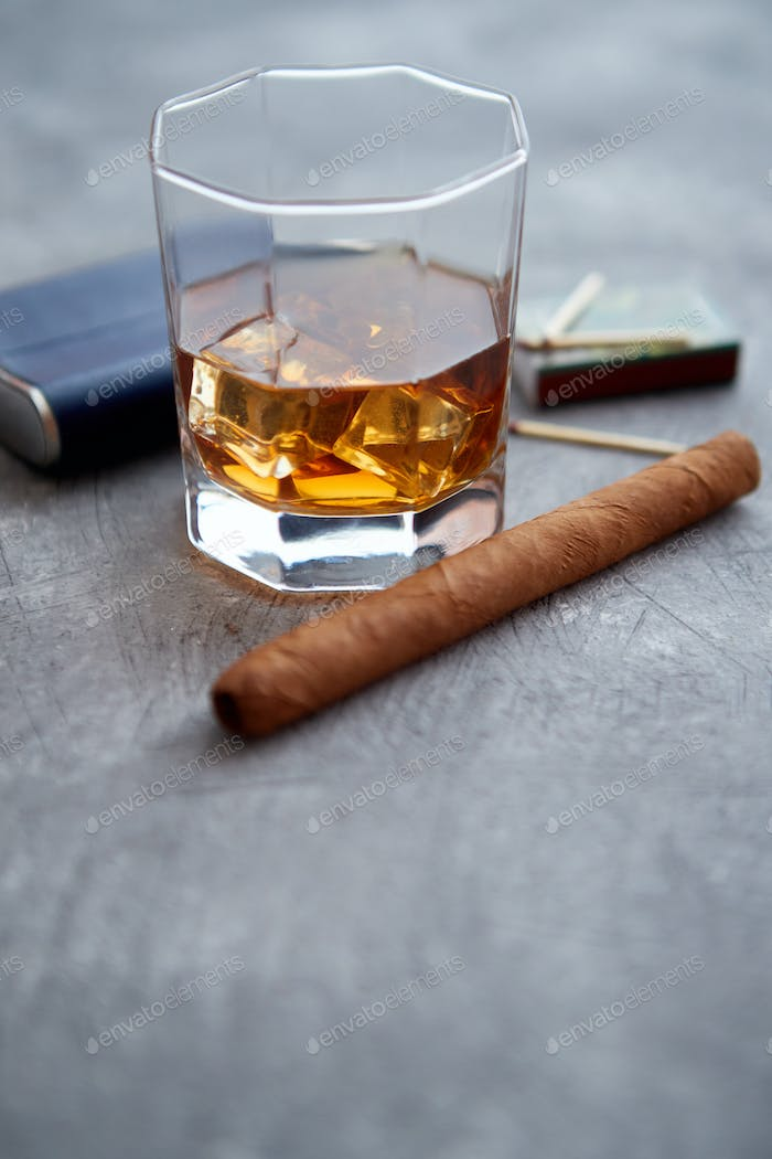 Glass of whiskey with ice, big cuban cigar, matches and hip flask