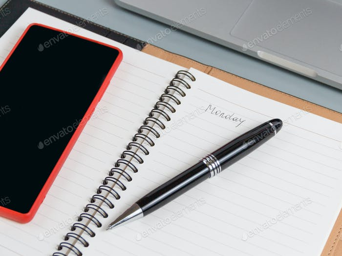 Opened agenda with handwritten MONDAY on a grey close up