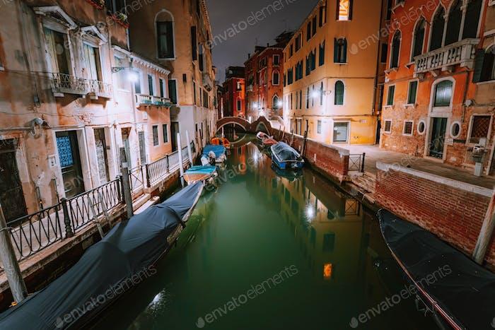 Venezia Italy. Narrow channel and gondola boats in lagoon city venice at night. Vivid colored old