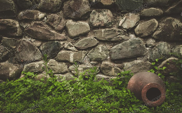 Stone wall texture background with ancient jar