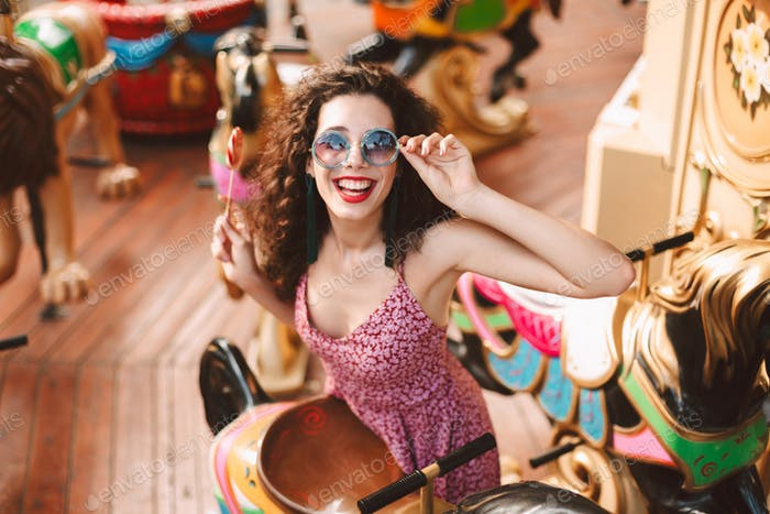 Happy lady in sunglasses with lolly pop happily looking in camera riding on carousel