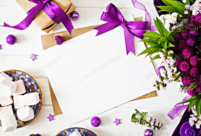 Mockup. Cards and flowers, box gift,violet ribbon and cloth lying on a white table