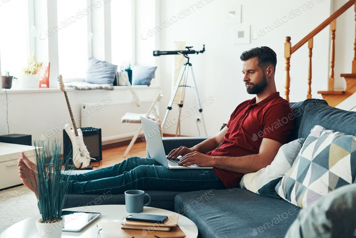 Charming young man in casual clothing using laptop while sitting on the sofa