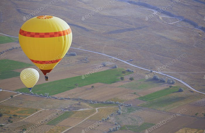 Two Yellow Air Balloons Flying Over the Land