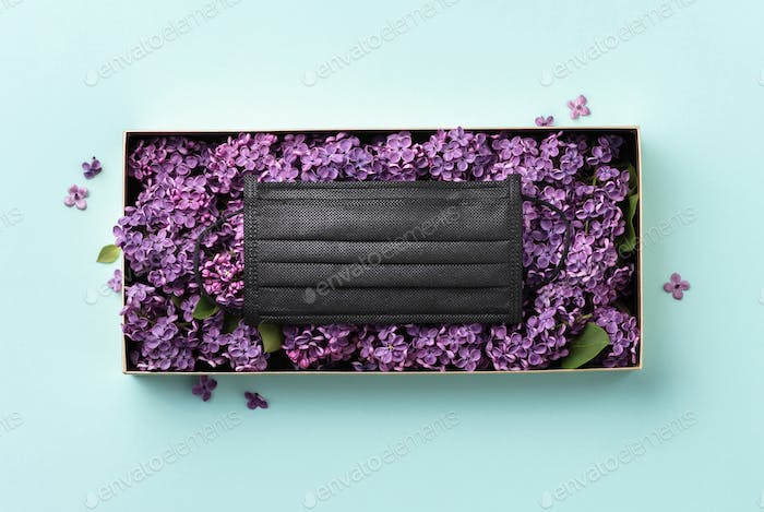 Black protective face mask in the box of flowers flat lay