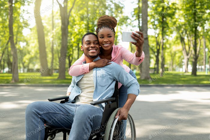 Happy black woman and her impaired boyfriend in wheelchair taking selfie together, hugging at city