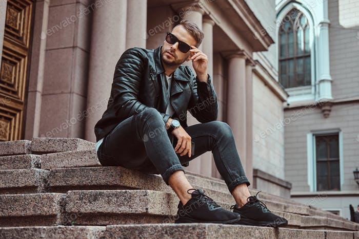 Fashionable guy dressed in a black jacket and jeans