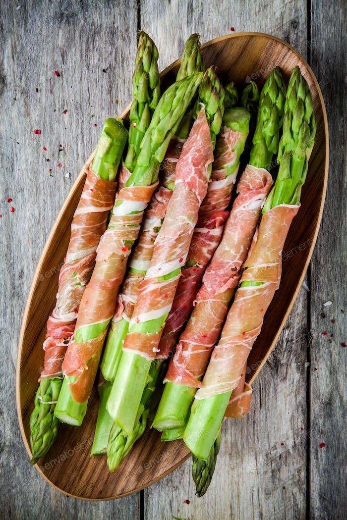 Fresh organic asparagus wrapped in Parma ham on a bowl