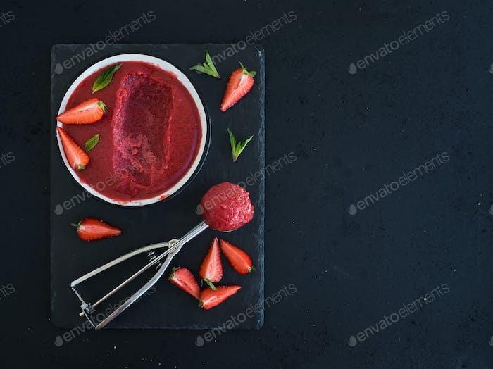 Erdbeersorbet oder Eis mit frischen Beeren, Minze und Metallschöpfer
