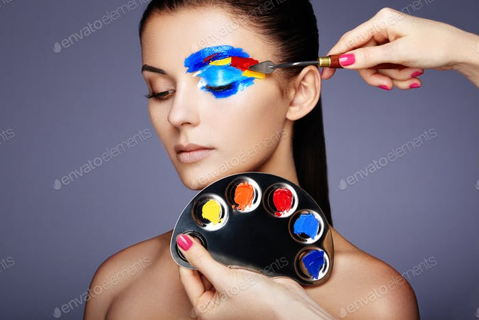 Makeup artist applies colorful makeup