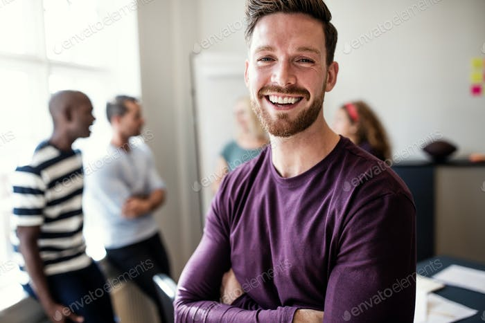 Laughing young designer standing in an office after a meeting