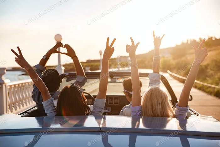 Happy friends in cabriolet with raised hands driving on sunset
