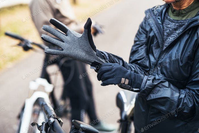 A midsection of active senior couple standing outdoors with electobikes, putting on gloves.