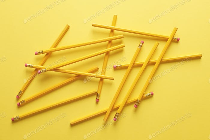 Plenty of pencils against yellow background