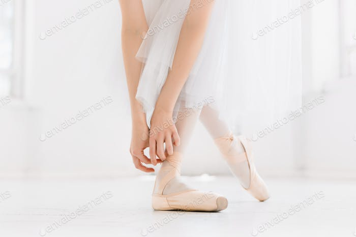 Young ballerina dancing, closeup on legs and shoes, standing in pointe position.