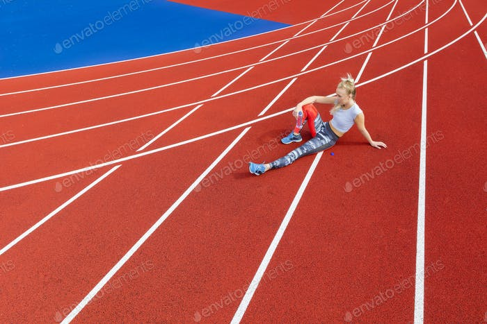 Athletic female runner rests on running track at sports arena