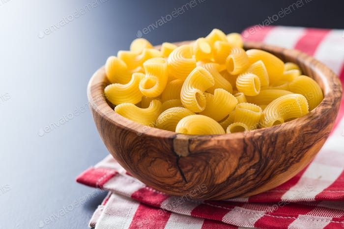 Uncooked elbow macaroni in bowl on checkered napkin.