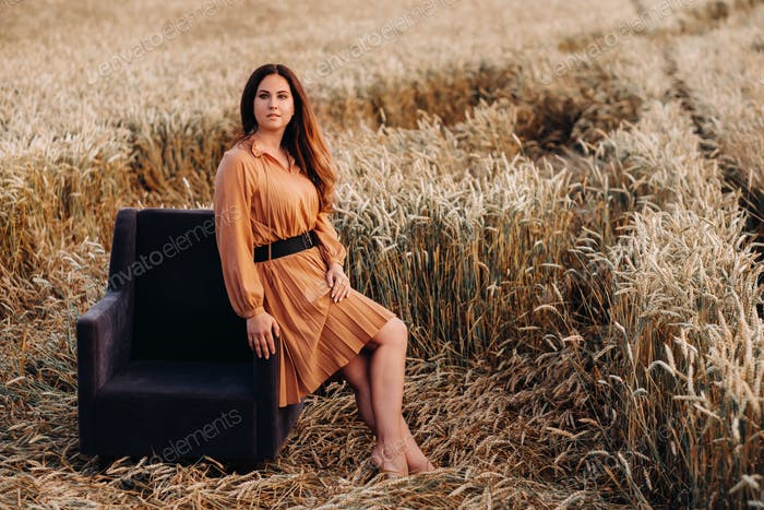 A girl in a orange dress is sitting on a chair in a wheat field in the evening