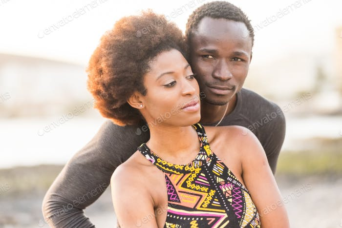 happy black race african couple at the beach in love and enjoying the leisure activity together
