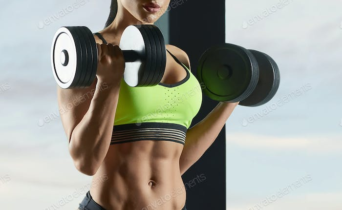 Cropped photo of strong fit model lifting in gym heavy dumbbells
