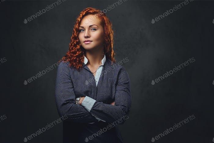 Rothaarige weibliche Supervisorin in einem eleganten Anzug gekleidet.